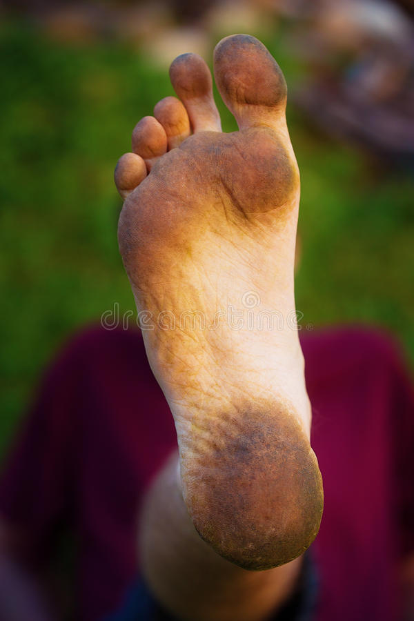 Dirty foot man on green background. stock image