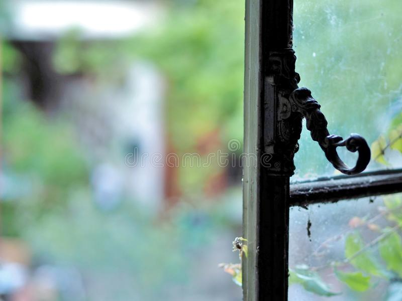 Dirty glass windows with antique window handle in old attic space. old, dirty, glass window panes covered in cobwebs. view outside royalty free stock images