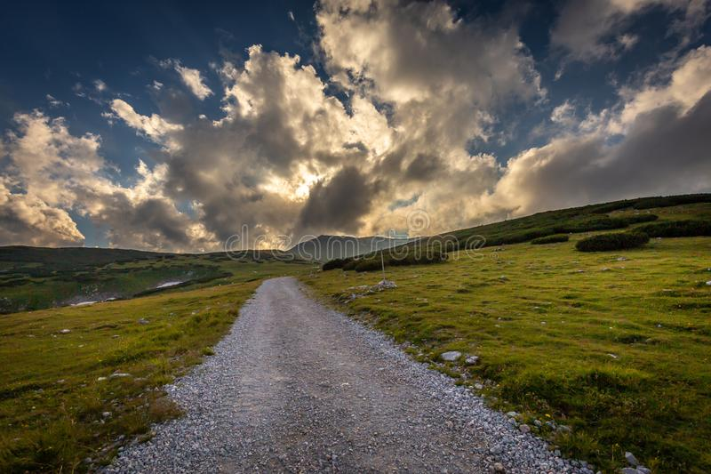 Dirty gravel road through fresh, green, grassy Alpine meadow to Dambockhaus and Fischerhutte from Puchberg royalty free stock image