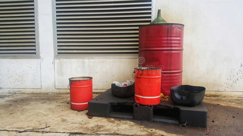 Dirty greasy barrels outside building with grease barrels. Disposed used oil on cover of barrel and spillage on floor royalty free stock photos