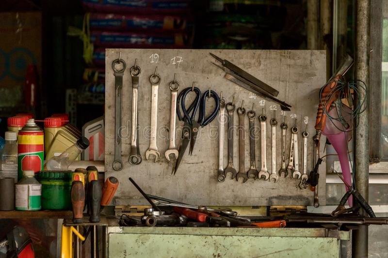 Dirty Greasy Set of Wrenches/ Spanners with Pairs of Black Scissors on an Old Wooden Rack - Messy Garage with Tools and Oil. Bottles/ Spray. Motorbike Repair royalty free stock photography