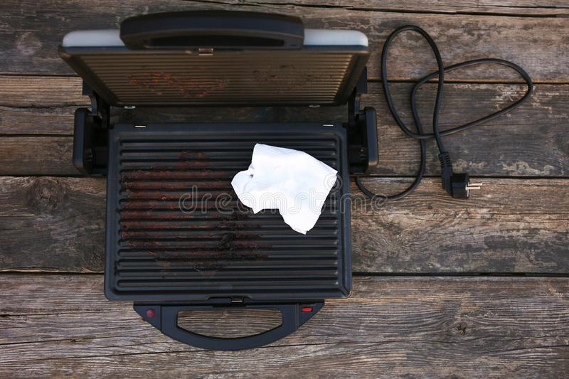 Dirty grill wiping with serviette. Dirty electric grill wiping with serviette royalty free stock images