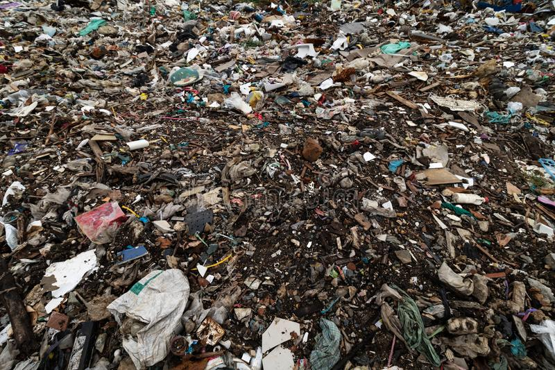 Dirty ground and filled with debris caused by the dumping from factories or industries and houses. Surface of a large amount of. Garbage or waste that piles up royalty free stock photo
