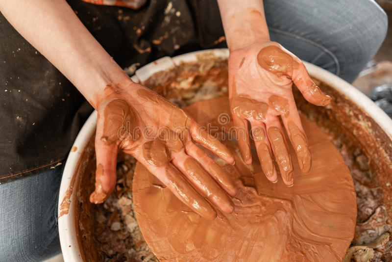 Dirty hand. Craftsman hands making pottery bowl. Woman working on potter wheel . Family business shop sculpts pot from. Happy woman working on potter wheel in royalty free stock image