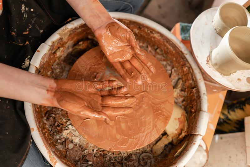 Dirty hand. Craftsman hands making pottery bowl. Woman working on potter wheel . Family business shop sculpts pot from. Happy woman working on potter wheel in royalty free stock photography