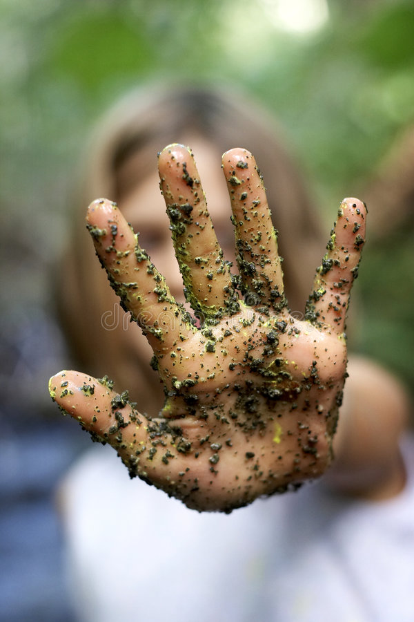 Dirty Hand held up in the stop position. A childs hand with paint and grains of sand and dirt, in the stop position, focus on the hand, very shallow depth of royalty free stock image