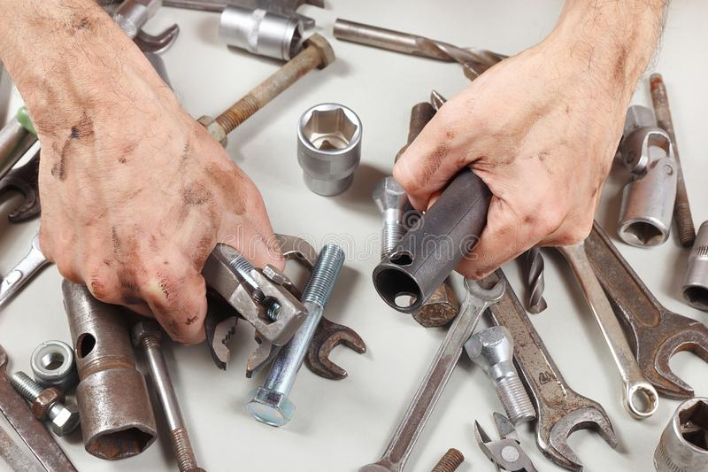 Dirty hand of master with tools for repairing machines in workshop royalty free stock image