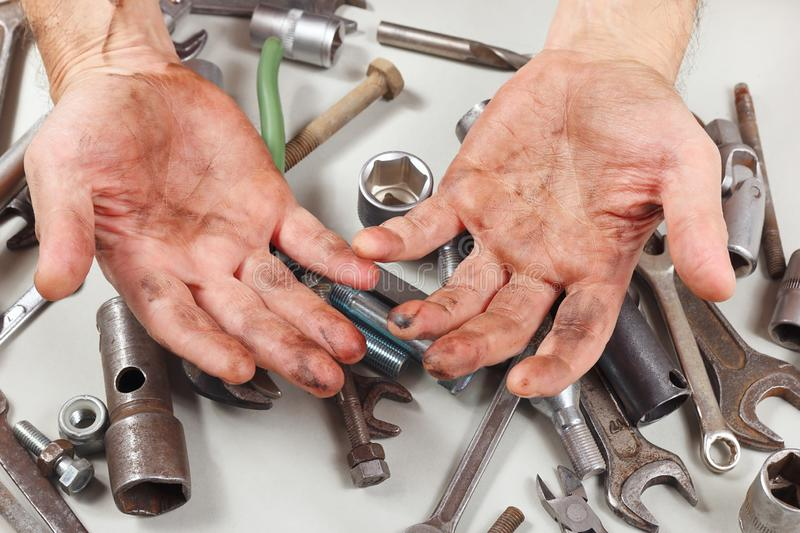 Dirty hand of repairman behind his work in workshop royalty free stock photography