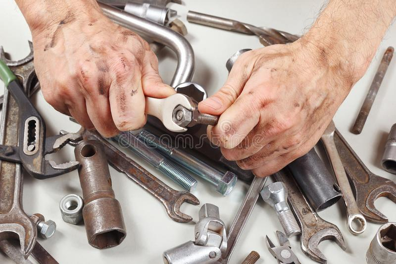 Dirty hand of repairman with wrench to tighten the nut royalty free stock images