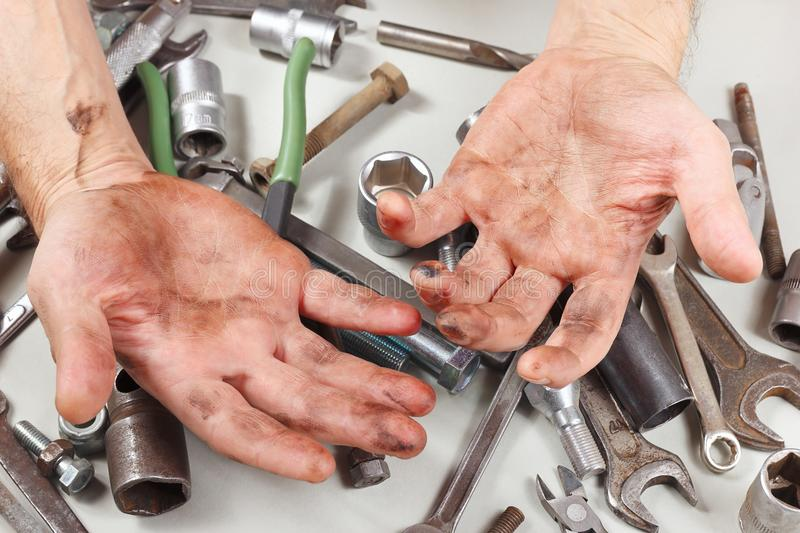 Dirty hand of serviceman behind his work in workshop royalty free stock photography