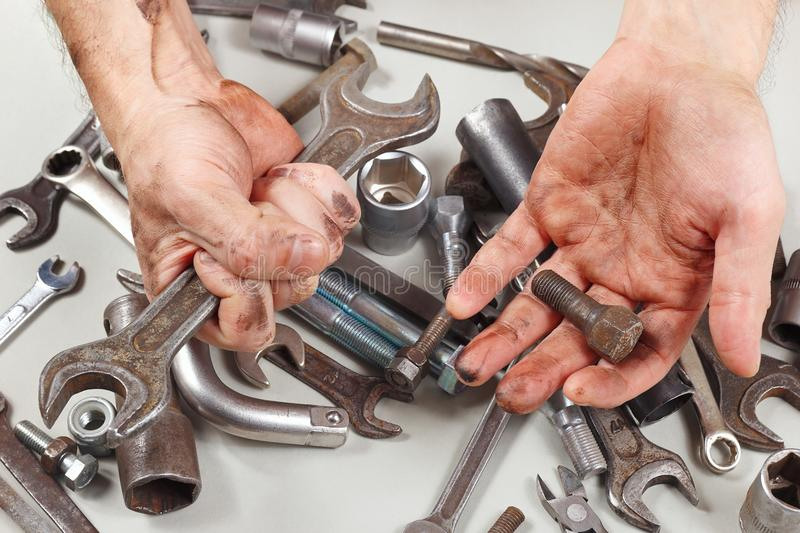Dirty hand of serviceman with tools for repairing machines in workshop stock photography