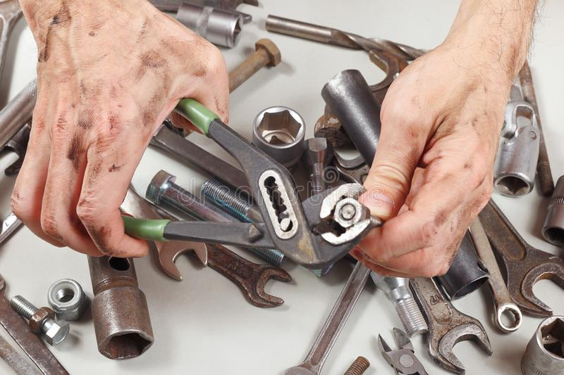 Dirty hand of serviceman with wrench to tighten the nut stock photos