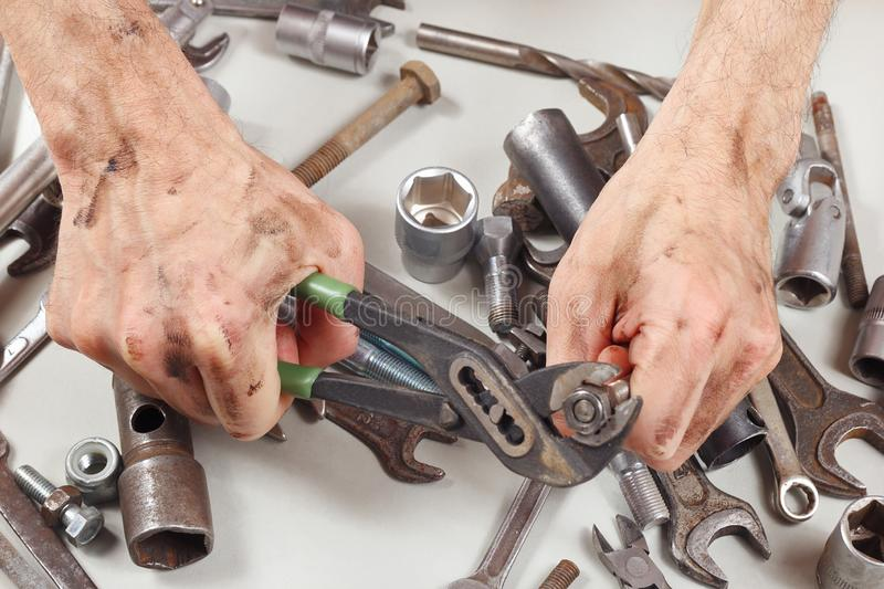 Dirty hand of worker with wrench to tighten the nut closeup royalty free stock images