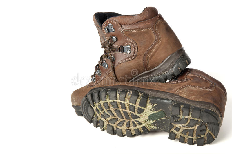 Dirty Hiking Boots. Dirty pair of hiking boots with grass and mud in the treads isolated on white stock images