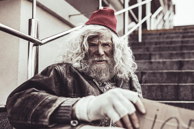 Dirty homeless man looking into the camera with doubt. stock image