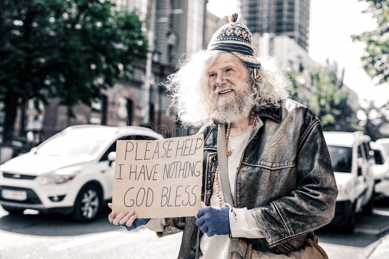 Miserable dirty old man being poor homeless and standing with cardboard stock image