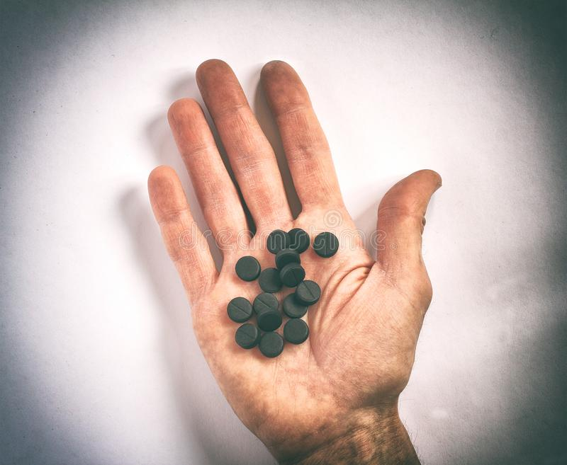 Dirty human palm with many of black pills royalty free stock photo