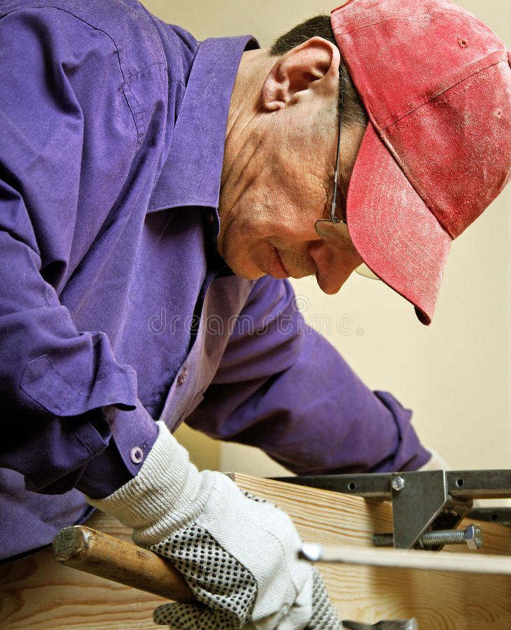 Dirty job. Carpenter with glasses is working royalty free stock image