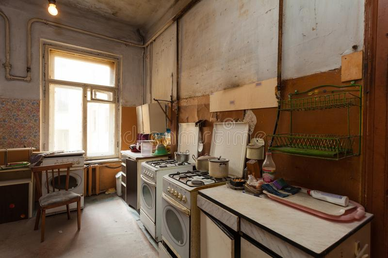 Dirty kitchen with furniture and gas stoves is in the apartment for temporary living existence refugees who were forced to mig stock photos
