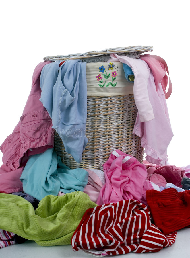 Dirty Laundry 2. A pile of dirty clothes overflows from a young girls laundry basket royalty free stock image