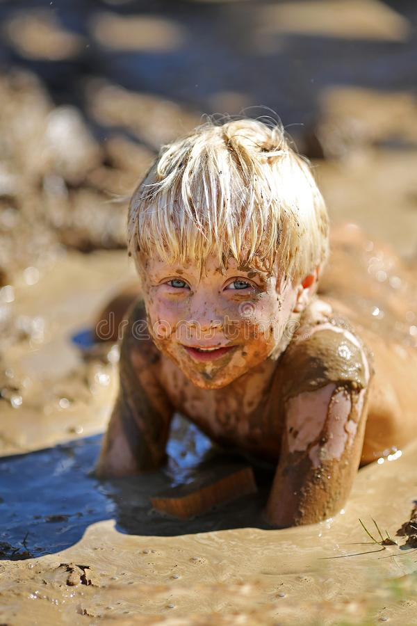 Free Dirty Little Child Laying In A Wet Mud Puddle Stock Photo - 99826540