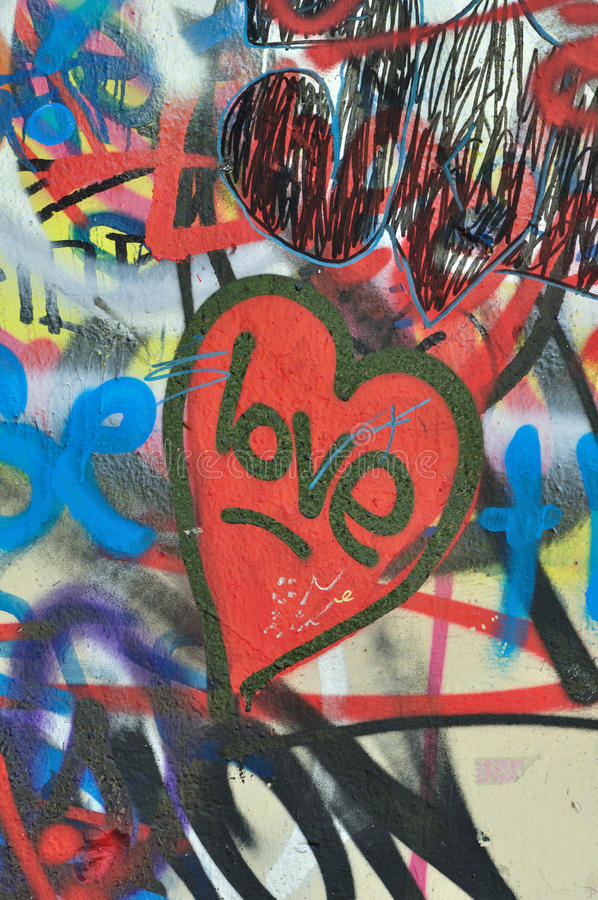 Dirty love graffiti urban background. Dirty love graffiti over messy tagged urban wall background. Heart of the city royalty free stock photo