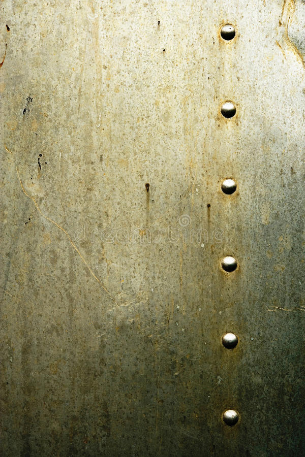 Dirty metal texture with rivets. Abstract background of a stained dirty metal surface texture with a line of rivets stock photos