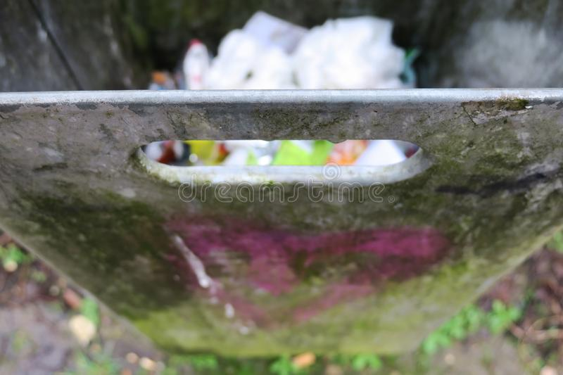 Dirty metal trash bin with and paper inside royalty free stock image