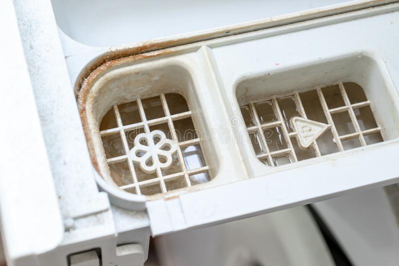 Dirty moldy washing machine detergent and fabric conditioner dispenser drawer compartment close up. Mold, rust and limescale in stock image