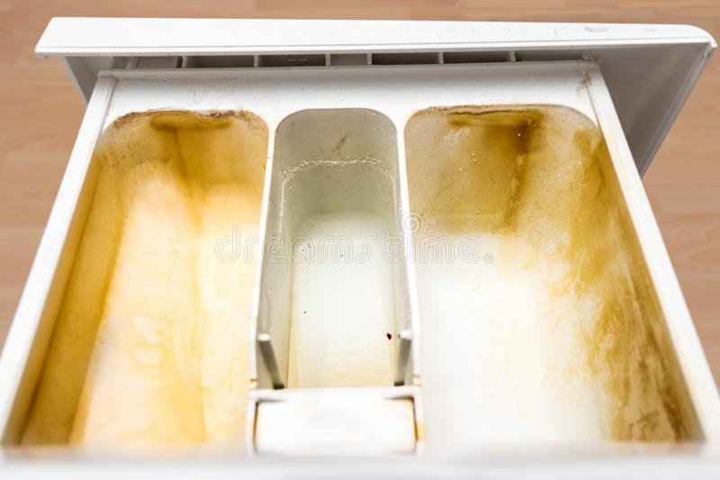 Dirty moldy washing machine detergent and fabric conditioner dispenser drawer compartment close up. Mold, rust and limescale in. Washing machine tray. Home royalty free stock images