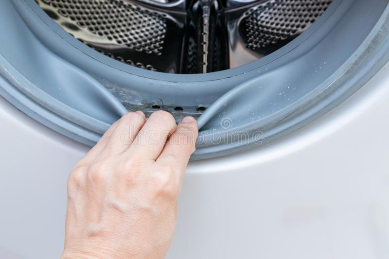 Dirty moldy washing machine sealing rubber and drum close up. Mold, dirt and limescale in washing machine. Home appliances stock photos
