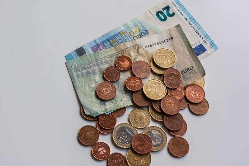 Dirty money euro banknotes and coins on white table. Dark business concept stock photo