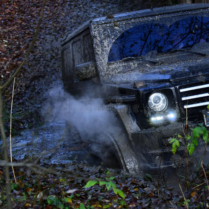 Dirty offroad car, close up. Powerful black car rides. With obstacles in forest area. SUV covered with mud stuck in puddle. Black crossover driving with cloud stock image