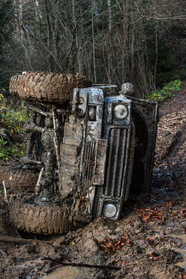 Dirty offroad car with dark forest on background. SUV rolled over on path covered with leaves. Crossover in dangerous situation. Impassibility of roads concept royalty free stock photography