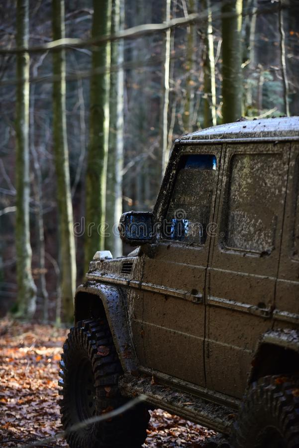 Dirty offroad car with fall forest on background. On sunny autumn day, defocused. SUV covered with mud on path covered with leaves. Tires, doors and windows stock photography