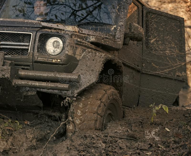Dirty offroad car with open door stuck in deep rut. Crossover covered with mud with fall nature on background. SUV goes through dirt, close up. Overcome stock photos