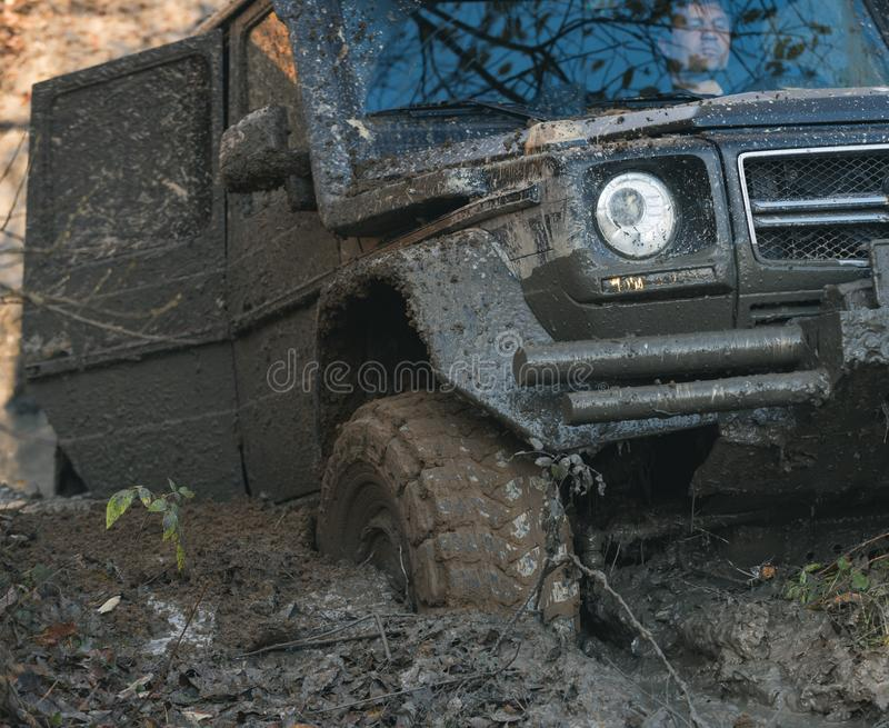 Dirty offroad car with open door stuck in deep rut. Crossover covered with mud with fall nature on background. SUV goes through dirt, close up. Overcome royalty free stock images
