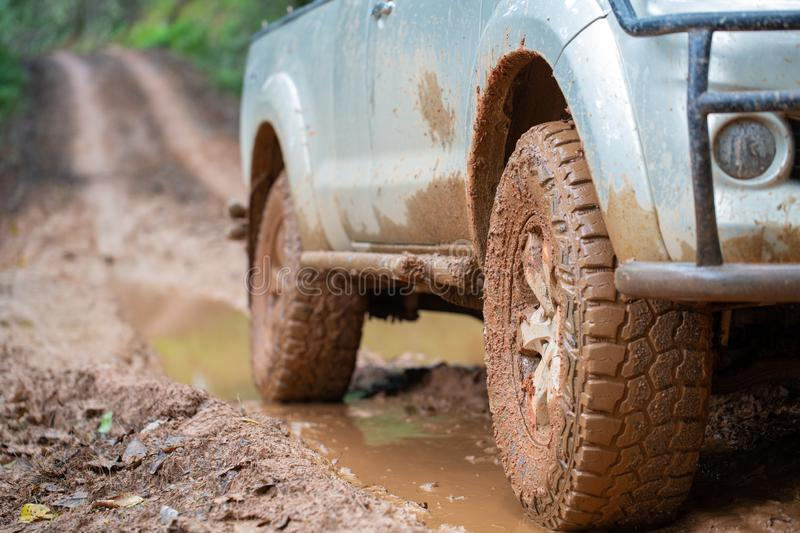 Dirty offroad car, SUV covered with mud on countryside road, Off-road tires, offroad travel and driving concept.  stock photography