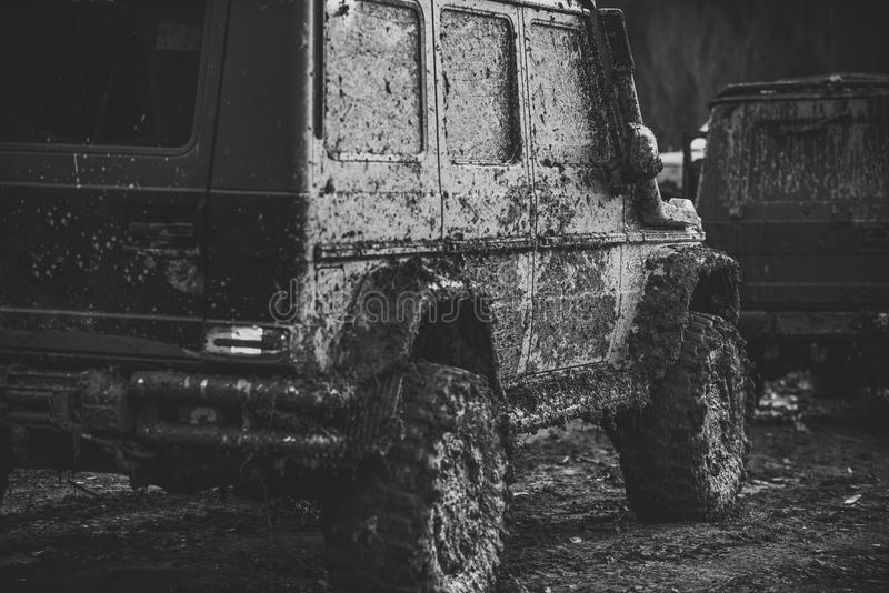 Dirty offroad cars on dark background, back view. SUV covered with mud with brake light turned on. Crossover after racing on countryroad. Extreme entertainment stock image