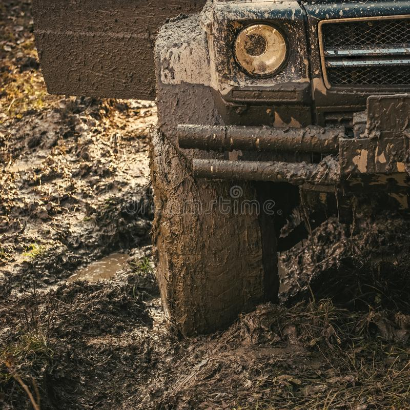 Dirty offroad tire covered with mud. Wheel in deep rut. Goes through mud and leaves trail. Extreme entertainment concept. Fragment of offroad car stuck in dirt royalty free stock photography