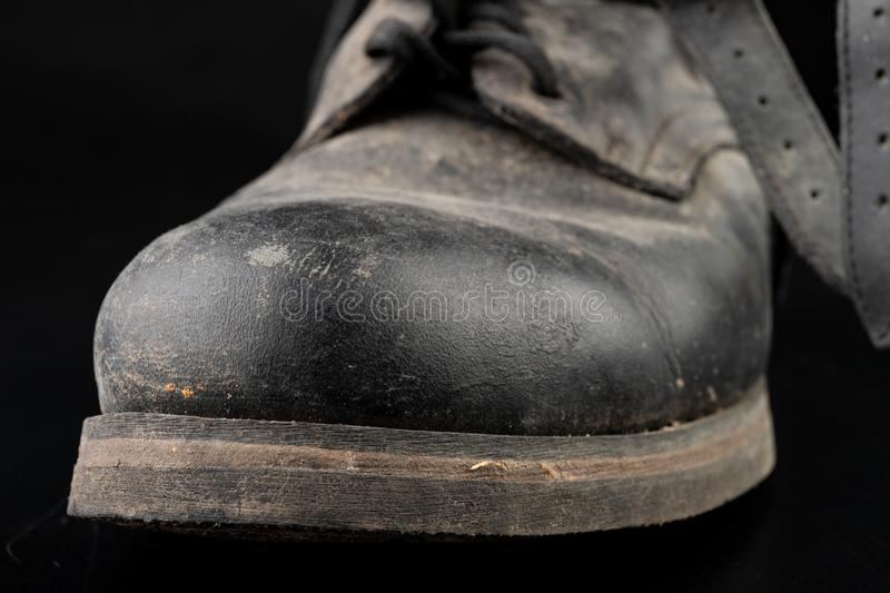 Dirty old black military boots from the mud. Footwear resistant to difficult terrain conditions royalty free stock photography