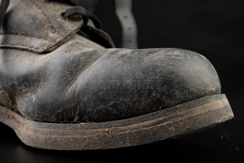 Dirty old black military boots from the mud. Footwear resistant to difficult terrain conditions. Dark background abstract antique army casual closeup clothes royalty free stock photos