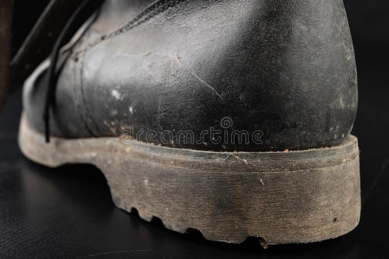 Dirty old black military boots from the mud. Footwear resistant to difficult terrain conditions. Dark background abstract antique army casual closeup clothes royalty free stock photo