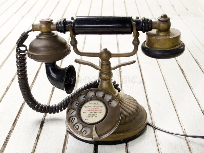 Dirty old classic retro style analog telephone. On white desk stock images