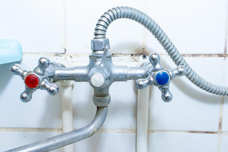 Dirty old faucet with limescale or lime scale on it, dirty calcified and rusty shower mixer tap and hose, moldy tiles on royalty free stock image