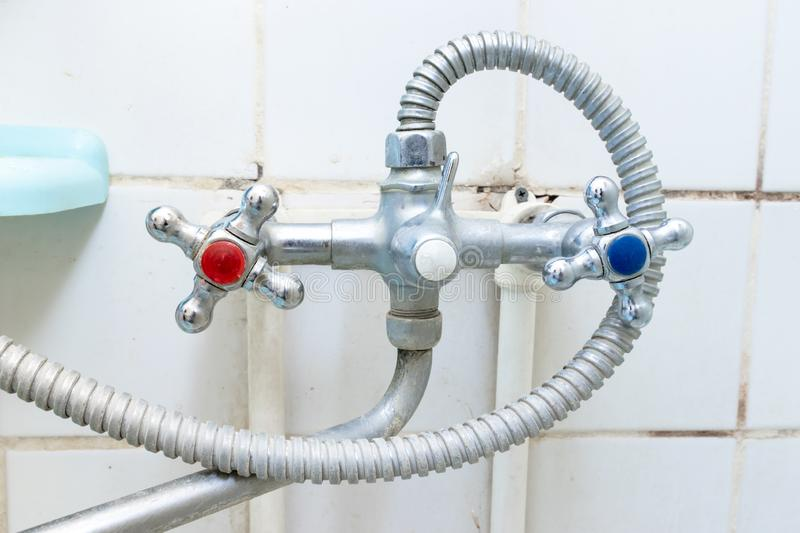 Dirty old faucet with limescale or lime scale on it, dirty calcified and rusty shower mixer tap and hose, moldy tiles on stock photography