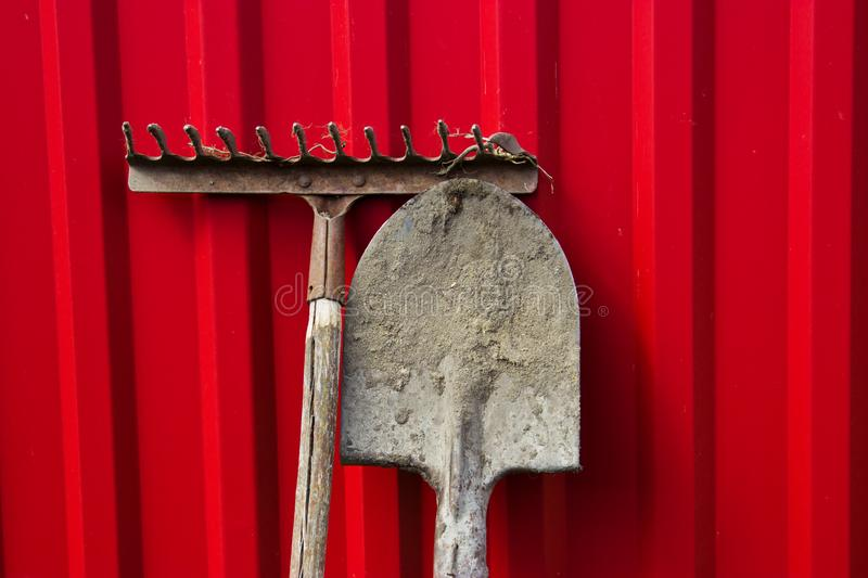 Dirty old rake and shovel on the background of the red fence. royalty free stock images