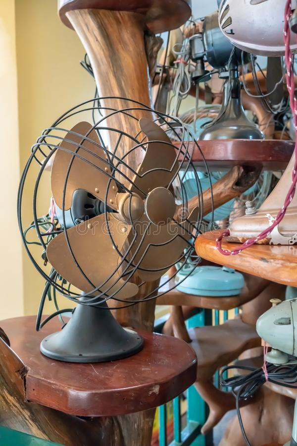 Dirty old vintage metal fan in retro style on wooden table royalty free stock photography