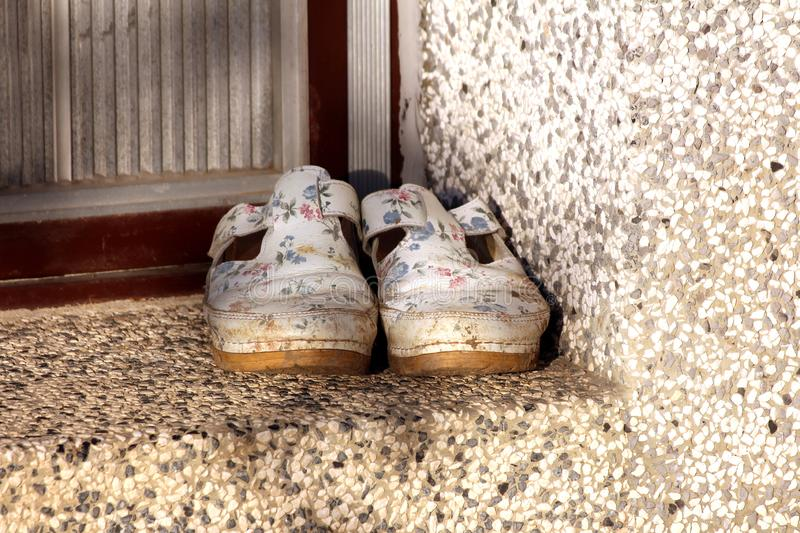 Dirty old woman shoes with flowers painted on white surface left in front of family house entrance doors at sunset stock photos