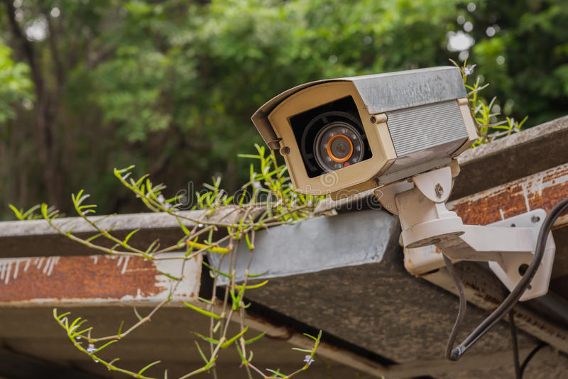 Dirty outdoor security camera and video on grass roof. Dirty outdoor security camera and video on grass roof,Concept for content royalty free stock photo
